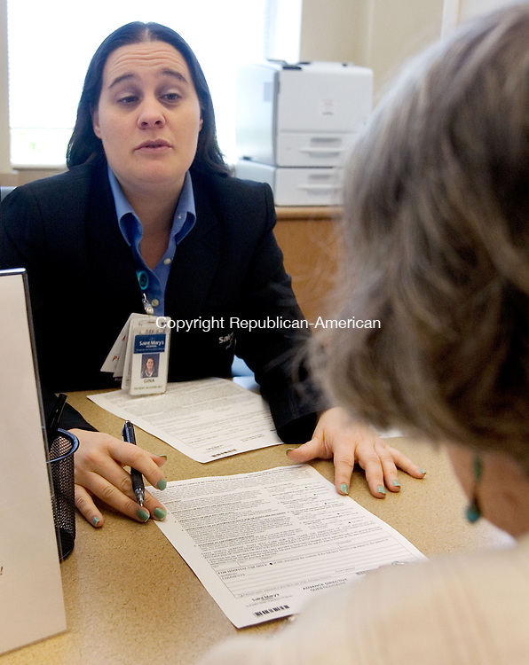 WATERBURY CT. 08 May 2015-050815SV09-From left, Gina Urbano, a patient access representative, registers Joan Vaughan of Southbury at St. Mary&rsquo;s Hospital in Waterbury Friday. <br /> Steven Valenti Republican-American