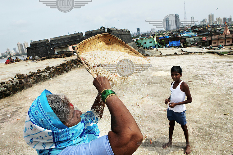 A woman filtering the sand from a basket of shrimps  in Worli Koliwada, one of the last Koli or fisherman's communities in Mumbai. The Kolis are a traditional fishing community whose links with Mumbai date back to the time when it was an archipelago of seven islands. The development of the city has marginalised the Kolis. Their villages are situated on prime commercial real estate and they are under pressure to leave their homes. Due to pollution, land reclaimation, destruction of mangroves and construction such as the new sealink bridge, the fishermen of Worli are catching fewer fish and their livelihood endangered.