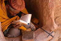 ETHIOPIA, Lalibela, rock churches built by King Lalibela 800 years ago, hermit sitting in tiny cave reading the bible in amharic script