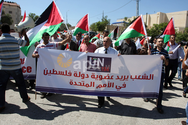 Palestinians hold banners and flags as they march during the launch of a campaign supporting a bid for Palestinian statehood recognition at the U.N, in the West Bank city of Ramallah on Sep. 8, 2011. A member of the campaign handed a letter intended for the U.N. secretary-general ahead of Palestinian President Mahmoud Abbas's bid to gain statehood recognition at the U.N. later this month. The banner reads: The people want Palestinian statehood membership at the U.N. Photo by Issam Rimawi