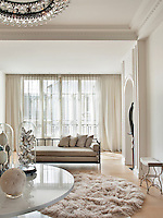 The elegant entrance hall of a stylish apartment decorated in neutral tones. Glassware pieces are displayed on an Angelo Mangiarotti pedestal table and a Jacques Adnet daybed is placed in front of the window.
