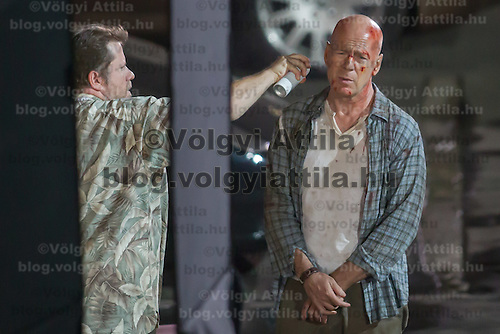 US actor Bruce Willis (R) is being prepared on set during a shooting of his next movie fifth in the Die Hard series titled Good Day to Die Hard in Budapest, Hungary on July 11, 2012. ATTILA VOLGYI