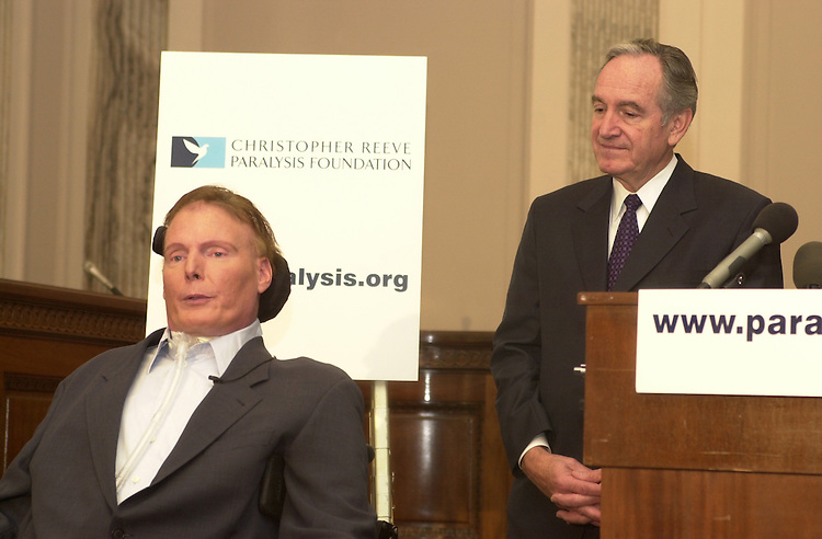 1superman101001 -- Senator Tom Harkin (D-IA) listens to Christopher Reeve on Wednesday before Reeve accepted his $2 million check from Secretary of Health and Human Services, Tommy Thompson.  Ther money is for the Christopher and Dana Reeve Paralysis Resource Center (PRC).
