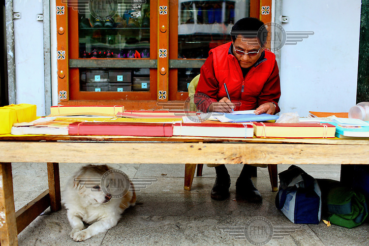 A monk does some paper work as a dog sits underneath his desk.