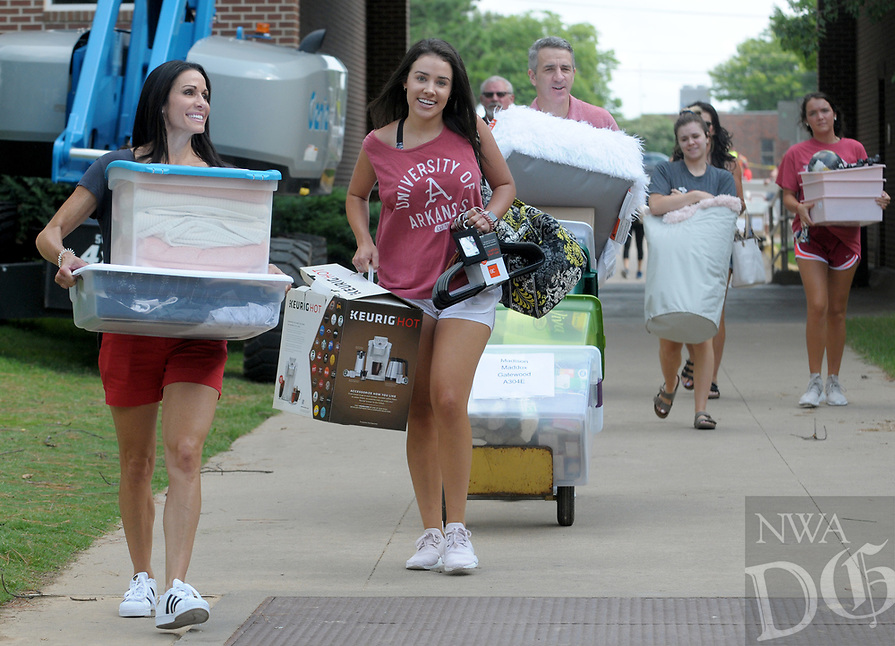 NWA Democrat-Gazette/DAVID GOTTSCHALK Madison Maddox (second from left) walks with her mother Mandy (left) and father John Thursday, August 9, 2018, as they carry items into her dorm room on the first day of Move-in for the 2018-2019 school year on the campus of the University of Arkansas in Fayetteville. University Housing coordinates the effort and staff expect more than 5,200 students to be moving into residence halls during this period.