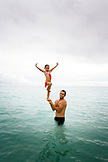 INDONESIA, Mentawai Islands, Kandui Resort, portrait of girl standing on his father's hands in the ocean