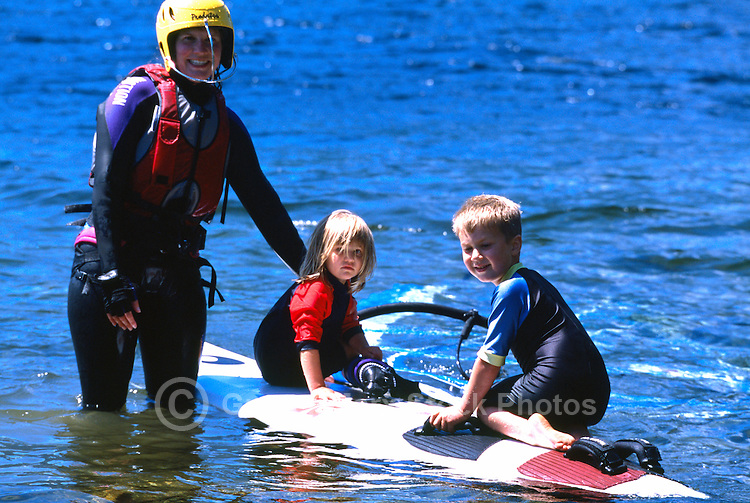 Woman windsurfing with Family on Nimpkish Lake, Vancouver Island, BC, British Columbia, Canada