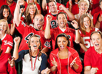 Extensive series of a crowd of fans inside a stadium watching their favorite football team.  Wearing team jerseys, having fun, eating, etc.
