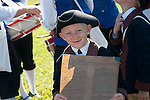 A boy from the Young Patriots Fife and Drum Corps holds the U.S. Constitution.