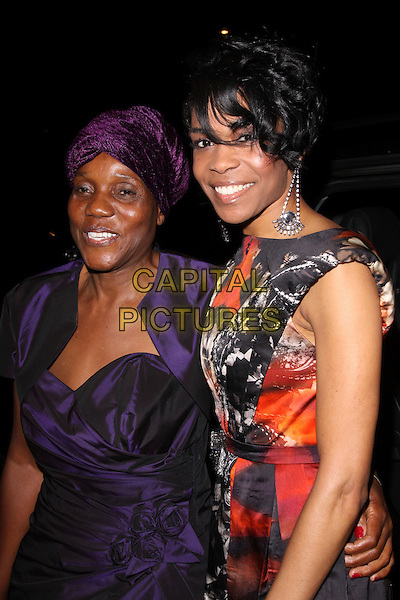 ROSELINE NDORO & MICHELLE WILLIAMS (Ex Destiny's Child).The Ndoro Children's Charities fundraising gala at The Dorchester Hotel, London, England. .September 17th, 2009 .half length red black white print dress sleeveless purple turban hat hair dangling silver earrings .CAP/AH.©Adam Houghton/Capital Pictures.