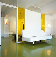 A 'Zzofa' sofa bed by James Irvine sits against a partition wall fitted with yellow glass panels that separates the bedroom from the living area