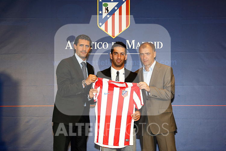 Atletico de Madrid's new player Arda Turan (c) during his official presentation with the General Manager Jose Luis Perez Caminero (l) and the Technical Secretary Milinco Pantic (r). August 16, 2011. (ALTERPHOTOS/B.Echavarri)