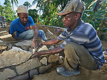 Saintorick Joseph (left) and Ernst Beouchamp place stones in the foundation of a house being built by Church World Service for a family that lost their home in Lareserve, a village near Jean-Rabel in northwestern Haiti, during Hurricane Matthew in 2016.  <br /> <br /> CWS is a member of the ACT Alliance.