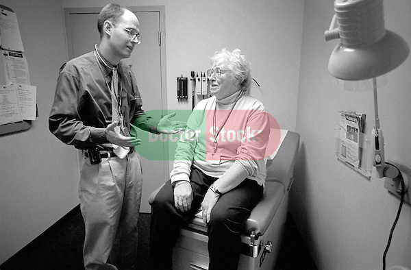 Young male doctor speaking with elderly female patient in examination room