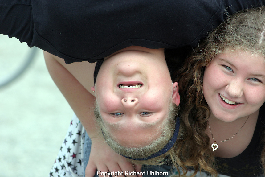A young boy and girl pose for a funny portrait on a school playground.