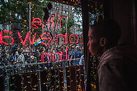 NEW YORK JUNE 13: A man looks at the crowd through the window of  the Stonewall Inn, a historic New York City gay bar during the celebration of a vigil to pay tribute to the victims of the massive shooting in a gay nightclub in Orlando, Florida. New York June 13, 2015<br />  Photo by VIEWpress/Maite H. Mateo.