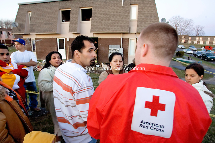 WATERBURY, CT--20 APRIL 2007--042007JS15-  Jesse Cunningham, Emergency Service Coordinator for the Greater Waterbury Chapter of the American Red Cross, center, talks with Miguel Torres, left, and his girlfriend Evelyn Gonzalez, of 182 Northridge Drive, apartment 5, and Evelyn Gonzalez, 48, of apartment 1, back left, following a fire inside their building in Waterbury on Friday afternoon. The girl on the right is unidentified. <br /> Jim Shannon / Republican-American