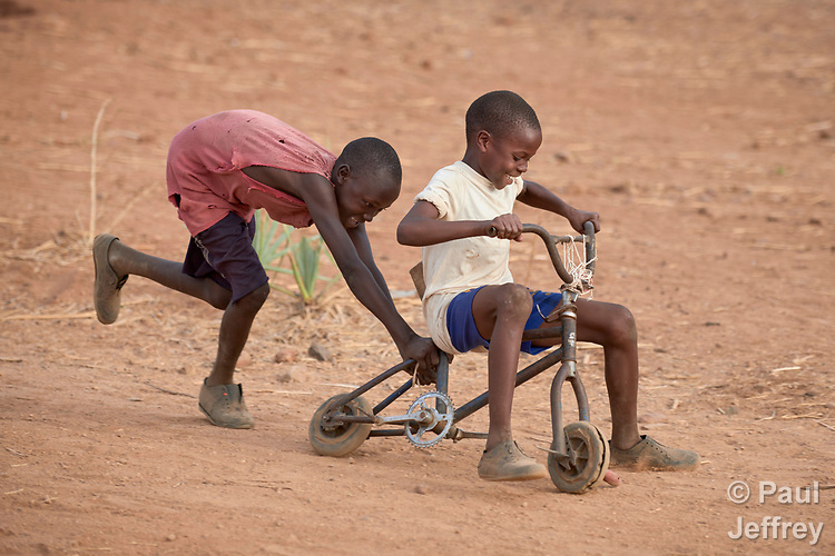 Boys play with a rehabilitated bicycle in Lugi, a village in the Nuba Mountains of Sudan. The area is controlled by the Sudan People's Liberation Movement-North, and frequently attacked by the military of Sudan.