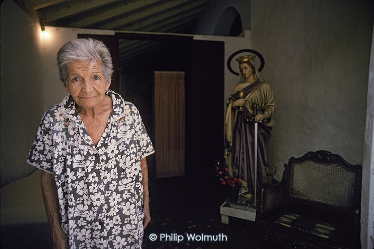 Elderly lady with a statue of the Virgin Mary in the southern town of Trinidad, which was declared a World Heritage site by UNESCO in 1988 to preserve the architectural legacy of its Spanish colonial history.