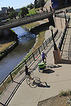 Parents riding bikes and pulling a baby carriage on a sidewalk in Denver, Colorado. .  John offers private photo tours in Denver, Boulder and throughout Colorado. Year-round.