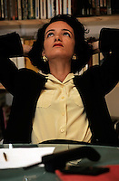 Business woman sitting at desk resting her head in her arms and thinking.
