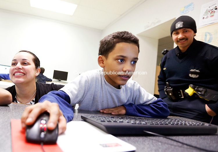 """Waterbury, CT- 13 March 2015-031315CM09- Jessica Ocasio, executive director at Rivera Memorial Foundation, left, looks on as brothers,  Anferny (cq) Bobadilla, 10 (off camera) and Anthony Bobadilla 9, right, play a math game on computers at the center in Waterbury on Friday. Looking on is Waterbury police officer and center volunteer, Matt Ocasio.  The foundation which mentors and provides after school activities for area children was founded in memory of Ocasio's father, Heriberto """"Eddie"""" Rivera, a Waterbury firefighter.   Christopher Massa Republican-American"""