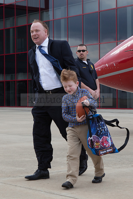 New University of Kentucky head football coach Mark Stoops and his son Zack stepping off his plane at the R.J. Corman Hanger in Nicholasville, Ky on December 2, 2012. Photo by Adam Chaffins | Staff
