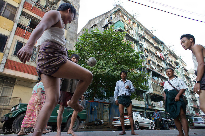 men playing with Rattan ball in the streets of Yangon, Myanmar, 2011