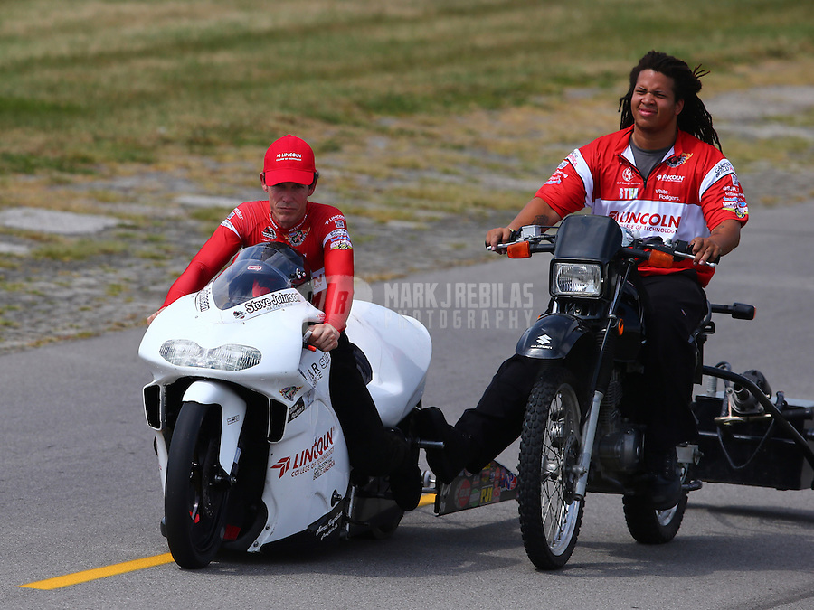 Aug. 31, 2013; Clermont, IN, USA: NHRA pro stock motorcycle rider Steve Johnson (left) with a crew member during qualifying for the US Nationals at Lucas Oil Raceway. Mandatory Credit: Mark J. Rebilas-