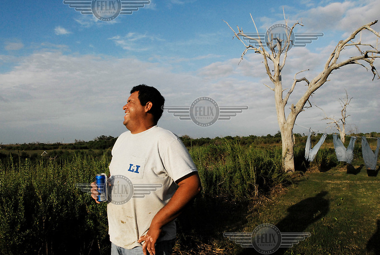 Walton Dardar Jr. stands in front of his home and drinks a can of beer in the predominantly Native American communtiy of Isle Jean Charles, Louisiana. Isle Jean Charles is one of dozens along the coast threatened by massive coastal erosion.