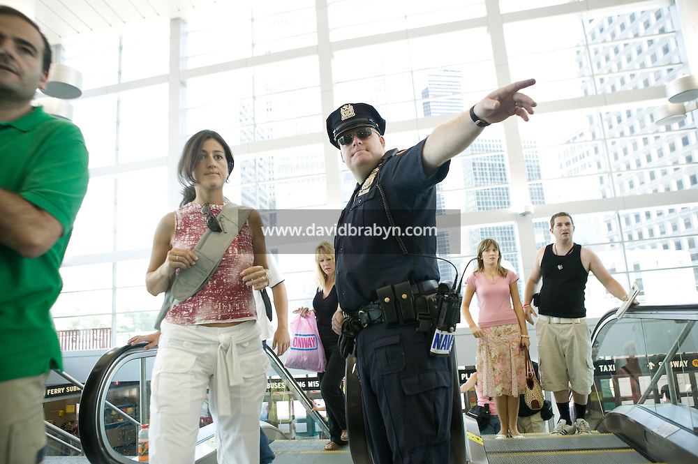 22 July 2005 - New York City, USA - Police officer A. Clarke ask a passenger to move to the side to have her bag checked as she enters the Staten Island Ferry Terminal in Manhattan, New York City, USA, 22 July 2005. The NYPD decided to subject riders to random bag inspections following the second attack on London's transit system in two weeks. Photo Credit: David Brabyn.