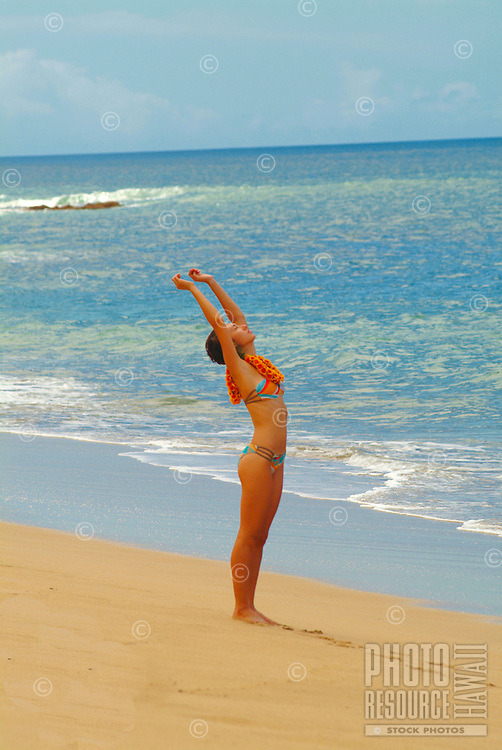 Young woman standing on the beach with arms outstretched