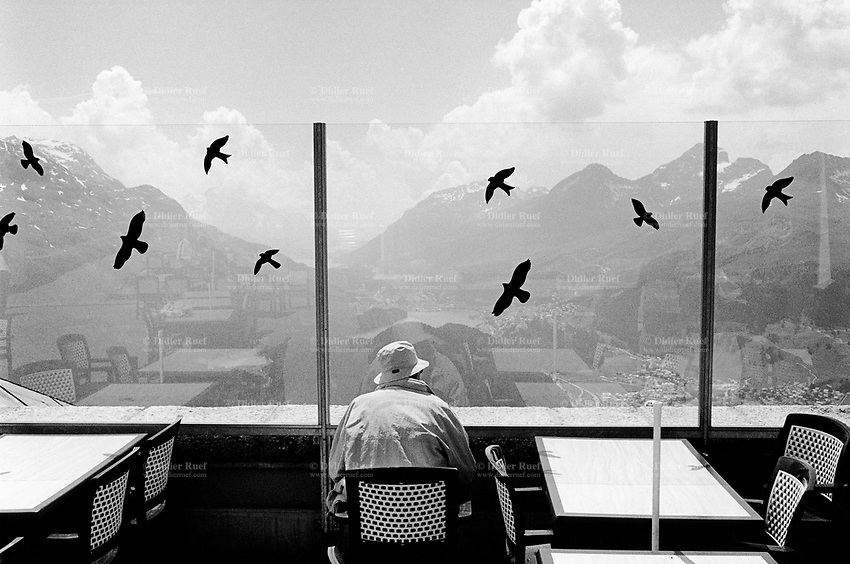 Switzerland. Canton Graubünden. Saint Moritz. View on the Upper Engadin valley. A man with a hat, seated on a plastic chair in an alpine restaurant's terrace, looks at the mountains panorama. Fake birds stickers are taped on the glass window to prevent real birds to fly into. © 2000 Didier Ruef
