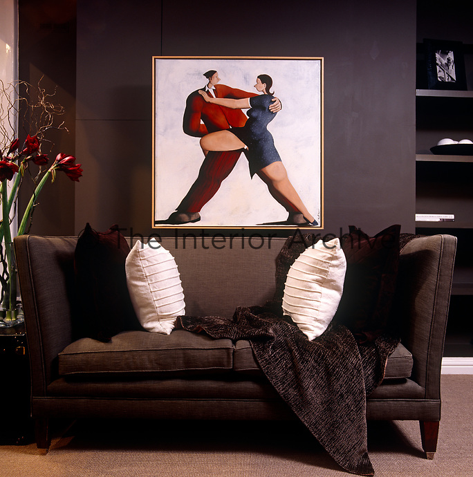 A painting depicting the tango looks down on a sofa covered in suede and linen cushions and a velvet throw in this living room