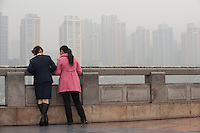 Two Woman Standing Next To A Wall Overlooking The Sunshine 100 New City Cityscape In Chongqing, China.  © LAN