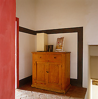 In the corridor a black frame is painted on the wall around an antique pine cupboard creating a dramatic focal point