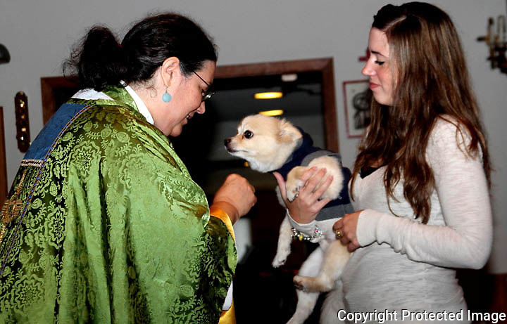 Reverend Laurie Rofinot gives the blessings to Janet Kingsbury and her Dog Charlie during the pet-friendly service at Trinity Episcopal Church in Stoughton Sunday October 6, 2013; the service was in honor of St. Francis of Assisi.