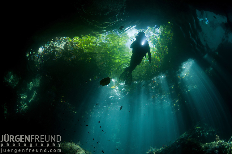 Shallow cave in dive site called The Passage with diver. North Raja Ampat, West Papua, Indonesia
