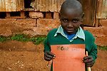 Kelvin shows off his math classwork at Hamomi Children's Centre in Nairobi, Kenya