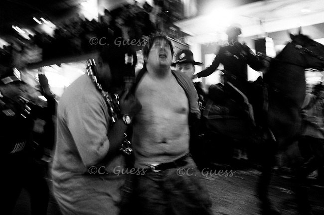 A party-goer gets taken away by members of the New Orleans police department on Bourbon Street on Fat Tuesday during Mardi Gras, 2008