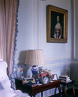 The colour of the delicate blue and white painted panelling in the bedroom is echoed in the Wedgwood bedside lamp and the fabric of the bed hangings