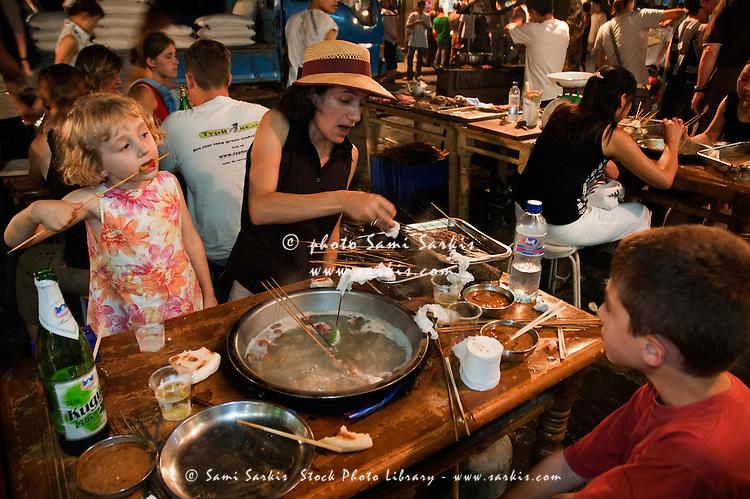 French family eating shish kebab on a restaurant terrace, Daqingzhen Si, Muslim District, Xian, Shaanxi, China.