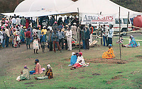 Dome-shaped temporary structures mark the location of  the Patients begin to line up for treatment at the AmeriCares clinic in Buranga, Rwanda, October 1994. The New Canaan Connecticut humanitarian organization set up their clinic on the road between Goma, Zaire (now Congo) and Kigali, Rwanda to help refugees returning from the camps in Goma and the people living in the area whose illnesses resulted from the destruction of what little infrastructure existed before civil war. (photo Rick D'Elia)