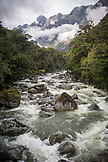 NEW ZEALAND, Fiordland National Park, Low Clouds and Mountains above a river in Milford Sound, Ben M Thomas