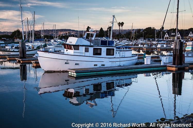 Ripples distort the reflection of a boat moored at the San Leandro Marina along San Francisco Bay.