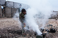 A soldier is pouring some alcohol on wood to light a fire and make some tea,Kunar, Afghanistan, 16th November 2017. <br /> <br /> Un soldat verse de l'alcool sur du bois pour allumer un feu et faire du thé, Kunar, Afghanistan, le 16 novembre 2017.
