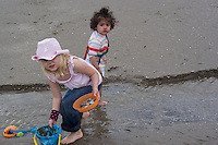 Safina paddling in water beside Morgan who's collected a sand filled bucket and a bowl of shells Bettystown beach 2nd Aug 2007
