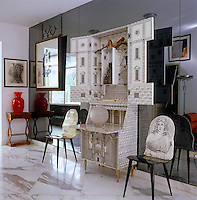 An unsual writing desk decorated with a trompe l'oeil motif alongside matching chairs with a painted back in a 20th century villa