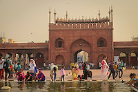 Visitors enjoy the pool in the courtyard of the Jama Masjid Mosque built of red sandstone and white marble.