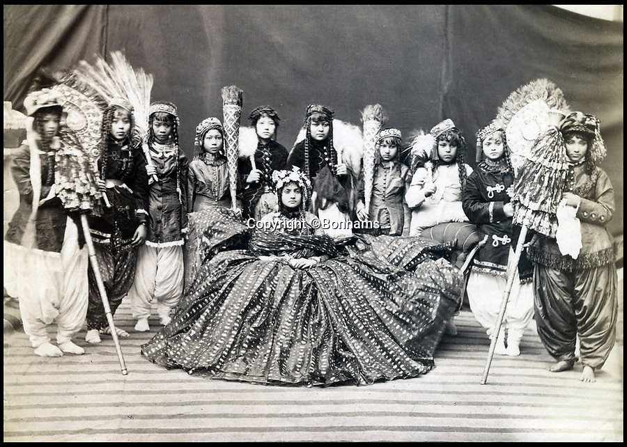 BNPS.co.uk (01202)558833<br /> Pic : Bonhams/BNPS<br /> A Nepalese female ruler with her maids of honour.<br /> <br /> Amazing portraits of Maharajas looking their most resplendent have come to light 150 years later.<br /> <br /> The snaps reveal the remarkably elaborate outfits worn by members of the Indian ruling class in the mid 19th century.<br /> <br /> One striking photo shows a Maharaja on horseback holding a long spear, while another is of an Indian ruler in his finery on his throne.<br /> <br /> There are also photos of Nepalese ladies of the court in spectacular dresses and high ranking British officials.